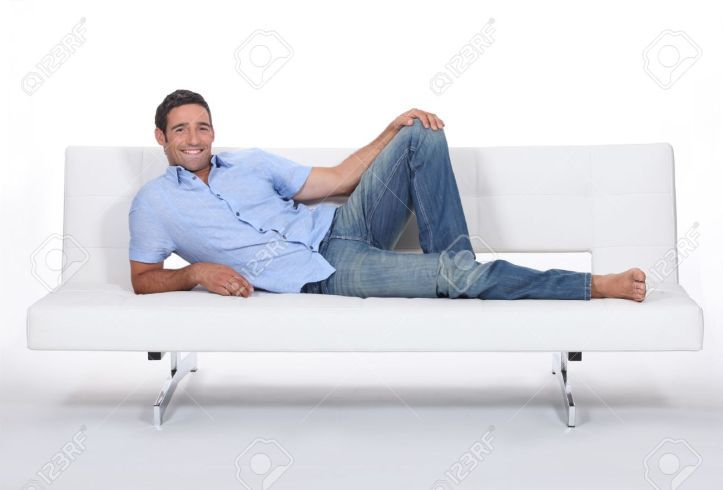 13621878-Barefoot-man-lying-on-a-couch-Stock-Photo-man-sofa